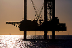 Offshore jackup oil drilling rig silhouette with at sunset.