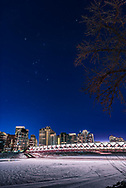 Orion on a clear winter night in downtown Calgary and shining over the pedestrian Peace Bridge  over the Bow River. I shot this on January 20, 2018. <br /> <br /> This is a real scene, though the sky is a single longer exposure of 6 seconds at ISO 400, while the ground is a blend of 4 exposures from 1.6 to 8 seconds at ISO 100, all at f/2.8 with the 24mm Sigma Art lens and Nikon D750. A NISI Natural Night filter helped cut through light pollution and provide a more natural blue sky, though this was a moonless night. The ground images were blended with luminosity masks generated with ADP Pro v3, to prevent the lights on the bridge from blowing out too much. <br /> <br /> Star diffraction spikes added with Astronomy Tools actions.