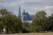 Two men do stretches on the grass with the skyline of the City of London's financial district, in Ruskin Park, on 8th August 2018, in London, England.