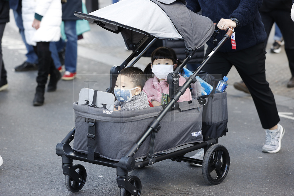 © Licensed to London News Pictures. 02/03/2020. London, UK. Small children wear face masks as they are pushed in a pram near Parliament. This morning Prime Minister Boris Johnson held a COBRA meeting to discuss the UK response to the coronavirus. Photo credit: Peter Macdiarmid/LNP