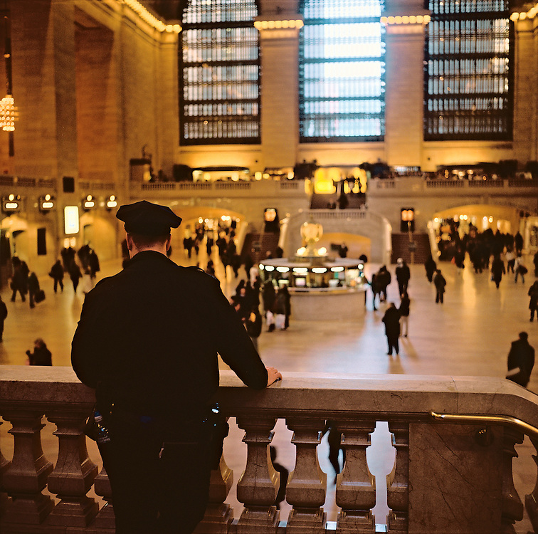 Police officer watching interior of Grand Central Terminal, New York