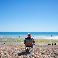 Coastal view with single male figure sitting alone on camping chair under blue sky and people enjoying the summer on the beach during lockdown in Worthing, West Sussex, England