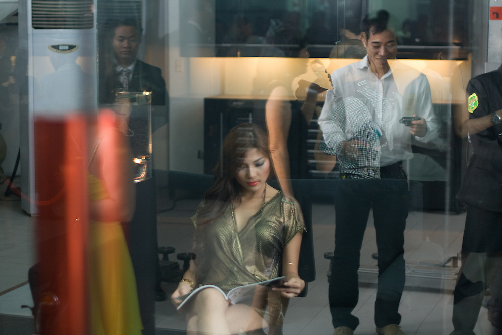 A model waits at the launch party of German luxury car Audi.In the background reflections of people attending this events. Business people and security.