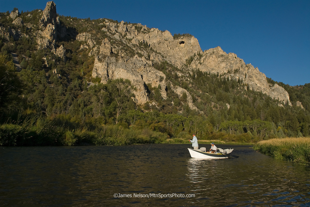 An angler fly fishes for trout from a drift boat during a summer afternoon on the South Fork of the Snake River, Idaho.