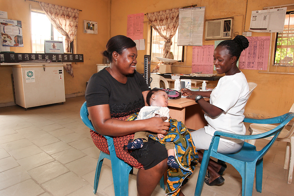 INDIVIDUAL(S) PHOTOGRAPHED: From left to right: Nkechi Jerome, Chew, and Adetoma Olubynmi. LOCATION: Onigbongbo Health Care Center, Lagos, Nigeria. CAPTION: A nurse gathers information from a woman about her baby son at the Ikeja Health Center, while making sure her other patients are in good spirits.