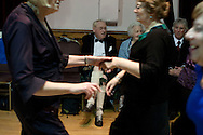 A man watching fellow guests dancing at a St. Andrew's dinner dance held by the Sandbach and District Caledonian Society at Sandbach Town Hall, Cheshire, England on St. Andrew's Day. Around 40 people from the Society attended the meal and dance which included a programme of Scottish country dancing. St. Andrew was the patron saint of Scotland and the day was celebrated by Scots worldwide on the 30th November.