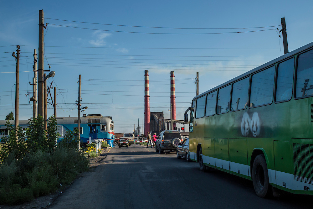 A bus transporting residents fleeing from fighting in nearby Horlivka waits at a train crossing before proceeding on to Simferopol, in Crimea, on Sunday, July 27, 2014 in Makiivka, Ukraine.