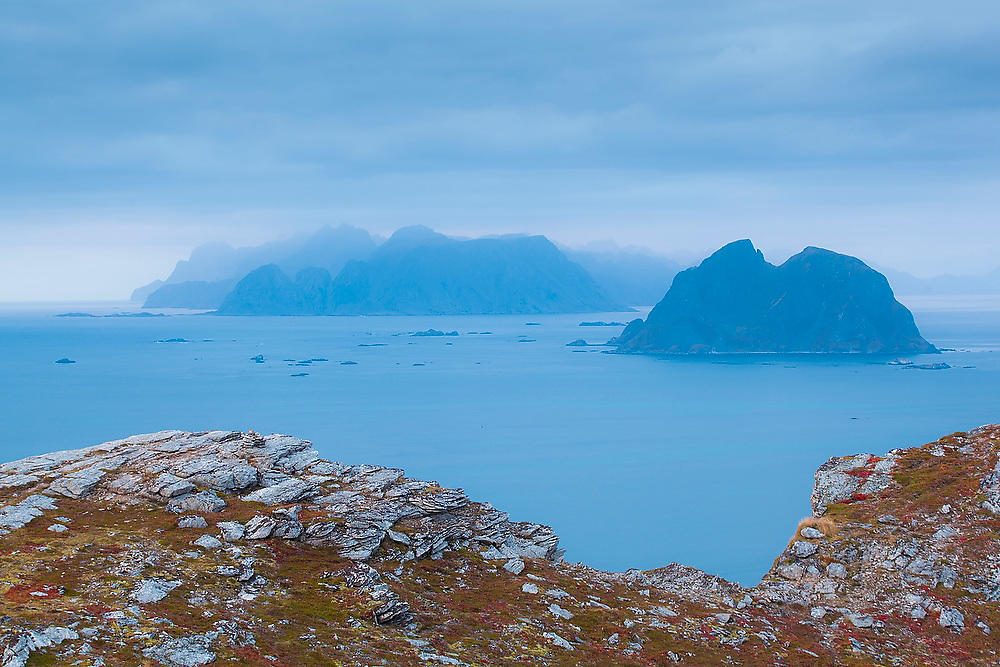 The islands of Mosken (right) and Moskenesoya at dusk, from Vaeroy Island, Lofoten Islands, Norway.