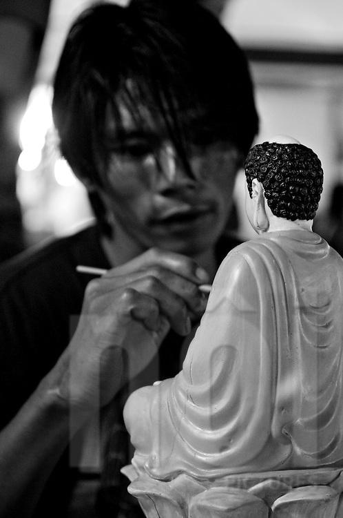 A Vietnamese man carefully paints a miniature Buddha statue. Nha Trang, Vietnam, Asia