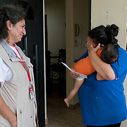 NOVEMBER 17, 2017&ndash;MARICAO, PUERTO RICO&mdash;<br /> Mercy Corps staffer Pardis Barjesteh, hands Stephanie Colon Medina, 27, an envelope with cash. Colon Medina is holding her 1 year old son Anthony Jaffeth.<br /> (Photo by Angel Valentin)