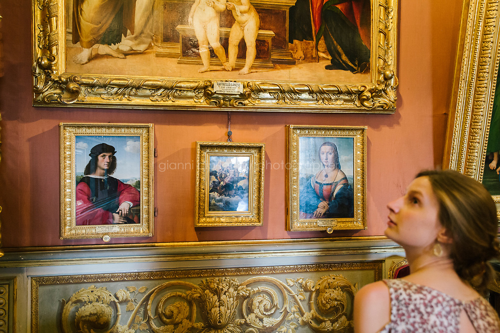 FLORENCE, ITALY - 3 JUNE 2018: A visitor is seen here by the dual portraits of Agnolo Doni and his wife Maddalena Strozzi, painted by Raphael round 1504-1505, here in the Hall of Saturn of Palazzo Pitti before the paintings will be relocated in room 41 of the Uffizi, in Florence, Italy, on June 3rd 2018.<br /> <br /> As of Monday June 4th 2018, Room 41 or the &ldquo;Raphael and Michelangelo room&rdquo; of the Uffizi is part of the rearrangement of the museum's collection that has<br /> been defining Uffizi Director Eike Schmidt&rsquo;s grander vision for the Florentine museum.<br /> Next month, the museum&rsquo;s Leonardo three paintings will be installed in a<br /> nearby room. Together, these artists capture &ldquo;a magic moment in the<br /> first decade of the 16th century when Florence was the cultural and<br /> artistic center of the world,&rdquo; Mr. Schmidt said. Room 41 hosts, among other paintings, the dual portraits of Agnolo Doni and his wife Maddalena Strozzi painted by Raphael round 1504-1505, and the &ldquo;Holy Family&rdquo;, that Michelangelo painted for the Doni couple a year later, known as the<br /> Doni Tondo.