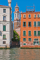 A church tower against a brilliant blue sky lies at the end of a narrow side canal in Venice, Italy.
