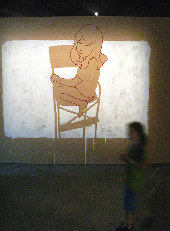 A young girl stands in front of a projected work of a young girl at the Venice Biennale 2009.
