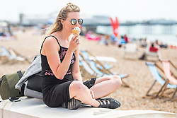 © Licensed to London News Pictures. 23/06/2018. Brighton, UK. 31 year old MANDY from Newcastle enjoys an ice cream on the beach in Brighton and Hove as sunny and warmer weather is hitting the seaside resort. Photo credit: Hugo Michiels/LNP