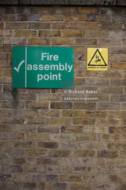 Cointradiction of Fire Assembly Point and Danger of Death signs.