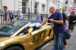 © Licensed to London News Pictures. 03/08/2019. London, UK. Supporters of Stephen Yaxley-Lennon, known as Tommy Robinson stick a sticker on a parked golden Lamborghini in central London. Last month Tommy Robinson was given a nine-month prison sentence at Old Bailey after he was found guilty of contempt of court. Photo credit: Dinendra Haria/LNP