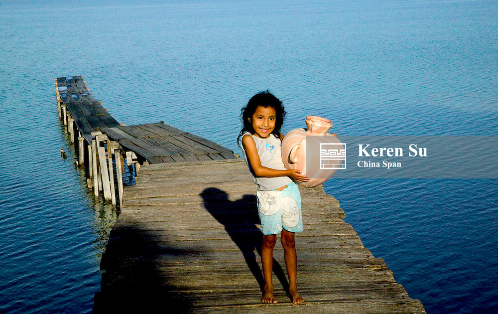 Little girl carrying jar by Lago Peten Itza, Remate, Guatemala