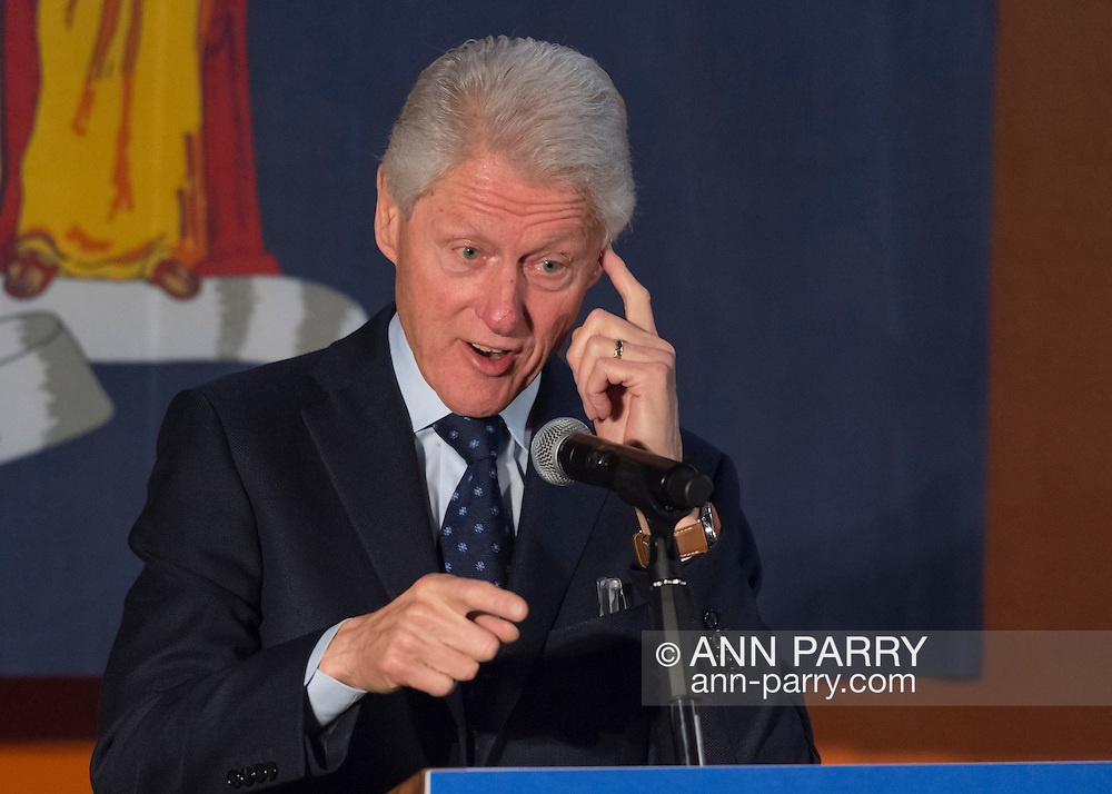 Elmont, New York, USA. April 5, 2016. Former President Bill Clinton, pointing one index finger toward audience, and touching other finger to his forehead while giving a speech, is the headline speaker as he campaigns at an Organizing Event rally in Elmont, Long Island, on behalf of his wife, Hillary Clinton, the leading Democratic presidential candidate, and former Secretary of State and U.S. Senator for New York. Podium has 'Fighting for us' slogan on sign. The New York Democratic Primary takes place April 19th.