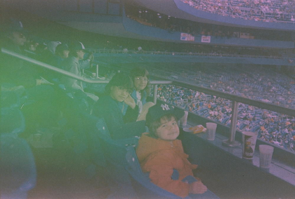 """When was this photo taken?<br /> <br /> I believe it was spring 1988<br /> <br /> Where was this photo taken?<br /> <br /> Yankee Stadium in New York<br /> <br /> Who took this photo?<br /> <br /> Most likely the girls' dad<br /> <br /> What are we looking at here?<br /> <br /> When our three daughters were between the ages of 4 and 11, as they are here, we lived in upstate New York and went to the city to visit my parents who lived on Long Island. It was If it was baseball season the girls always got to go to Yankee Stadium and it's with their dad that they learned to score the game, identify teams and enjoy the sounds and excitement of the ball park.<br /> <br /> How does this old photo make you feel?<br /> <br /> Looking at this photo today during the 2020 pandemic I am reminded how much of city life and the joy of visiting the city is wrapped up in the excitement of being in crowds. Will we ever know this feeling again?<br /> <br /> Is this what you expected to see?<br /> <br /> I didn't have any idea what would be on this roll of film. The quality doesn't surprise me because this roll sat around for over 30 years waiting to be developed. A reminder of how expensive it was to use film and have prints developed and how digital photography has changed all that.<br /> <br /> What kind of memories does this photo bring back?<br /> <br /> The girls loved these outings to baseball games. I didn't always go and suspect that I wasn't there that day. Greg, the girls' dad, loved baseball and made sure the girls loved it, too. It was their thing and when opening day came where we lived in upstate NY I heard that he would pick them up at school and sign them out for dental appointments, then drive up to the stadium for the opening day game. It was their """"secret"""" annual tradition.<br /> <br /> How do you think others will respond to this photo?<br /> <br /> I expect it will resonate with many family experiences others have also had."""