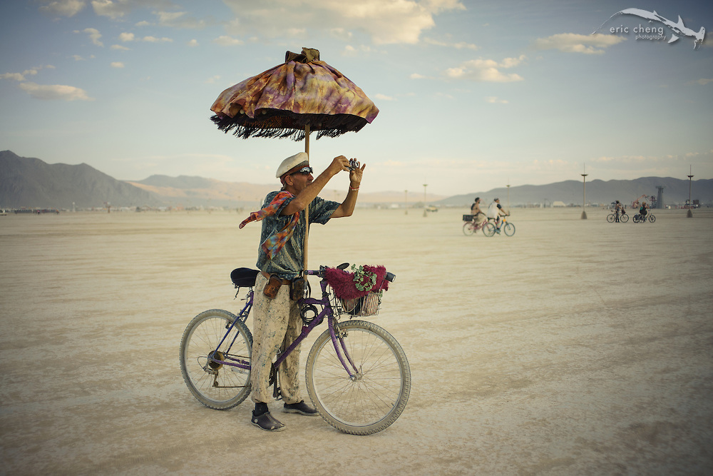 An old burner on a bike photographs The Man at sunset. Burning Man 2014