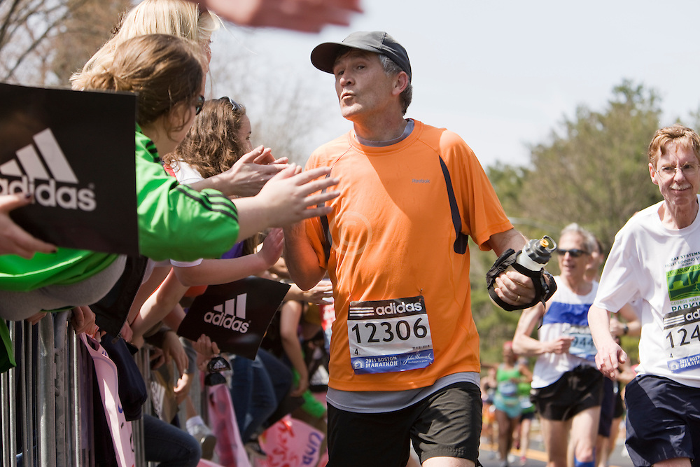 runner kissing the screaming girls as they line the course at Wellesley College near midpoint of race