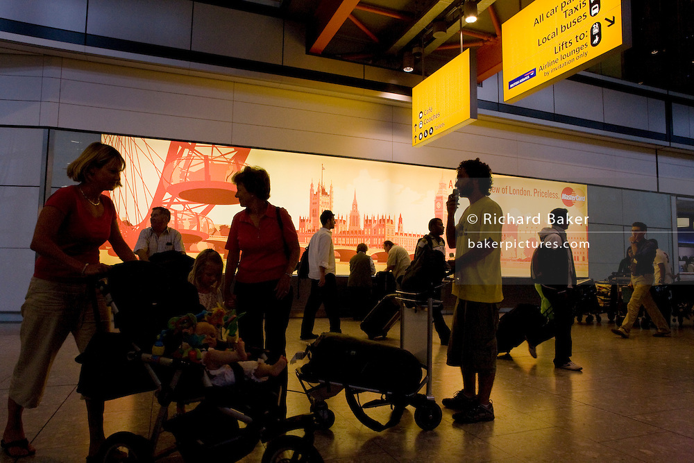 "Half-silhouetted figures add to the bustle of a hectic arrivals concourse at Heathrow Airport's Terminal 5. Seen against the orange advertisement for Mastercard which shows scenes of London that sightseers will want to visit. People wait for family to pick them up and tourists await the rest of their groups and tour guides with baggage trolleys laden with possessions. Terminal 5 has the capacity to serve around 30 million passengers a year. From writer Alain de Botton's book project ""A Week at the Airport: A Heathrow Diary"" (2009)."