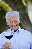 Senior man holding glass of wine, smiling