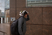 During a spring shower, a male commuter with head covered with a newspaper rushes over London Bridge during the evening rush-hour, from the City southwards to Southwark, on 3rd May, in London, England