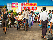 04 NOVEMBER 2015 - YANGON, MYANMAR:  A pedicab driver picks up a fare in front of a NLD poster in Dala, a working class suburb of Yangon. National elections are scheduled for Sunday Nov. 8 in Myanmar. The two principal parties are the National League for Democracy (NLD), the party of democracy icon and Nobel Peace Prize winner Aung San Suu Kyi, and the ruling Union Solidarity and Development Party (USDP), led by incumbent President Thein Sein. There are more than 30 parties campaigning for national and local offices.        PHOTO BY JACK KURTZ