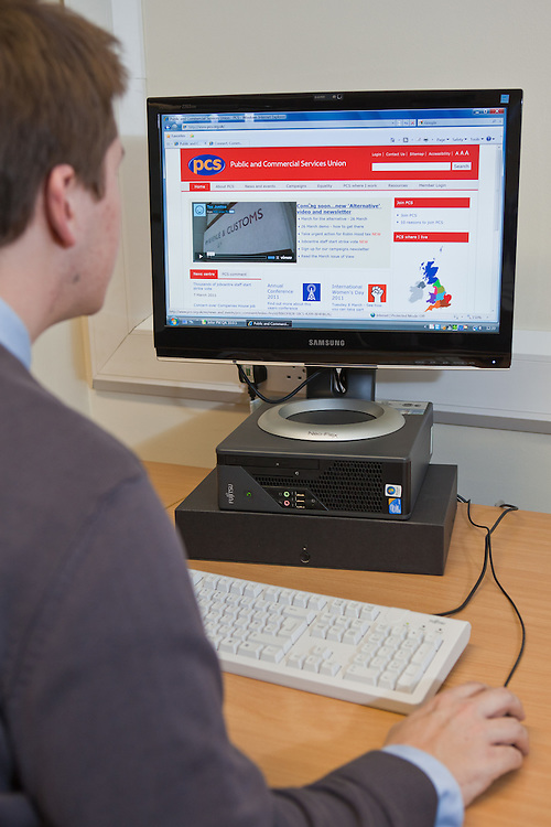 A young man using a PC computer to access the PCS website.