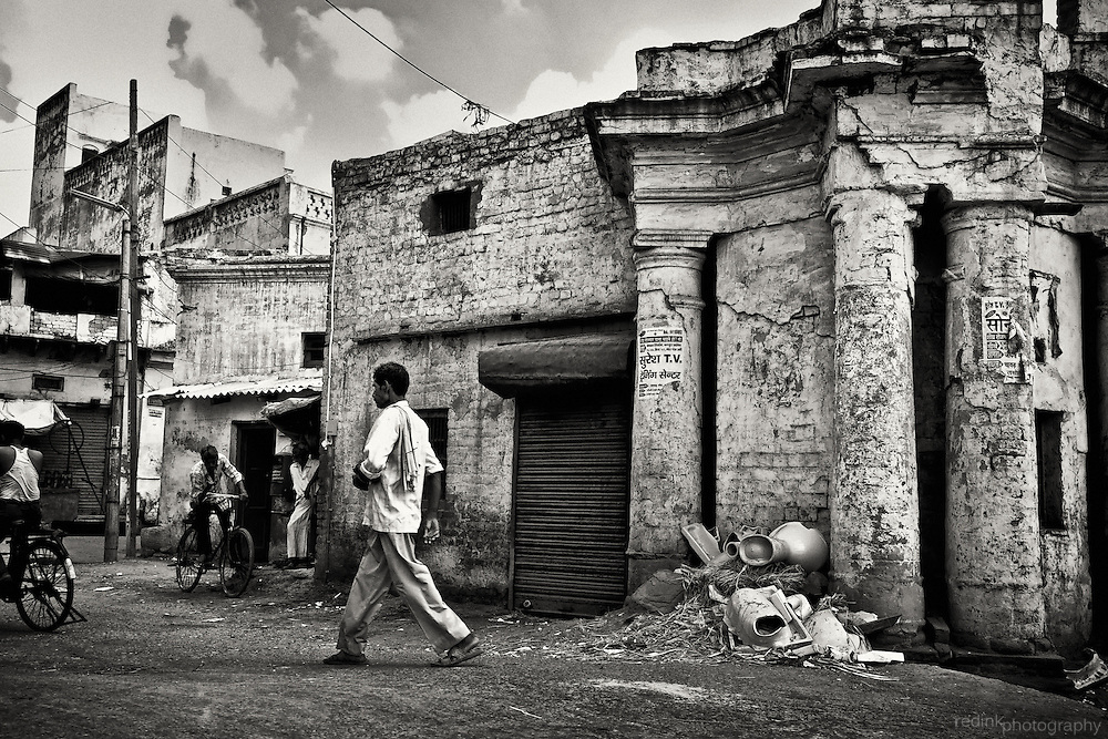 Portrait of an Agra side street near Mehtab Bagh. Crumbling building provides a backdrop for people walking and biking through the city street. Converted to black and white using Silver Efex Pro.