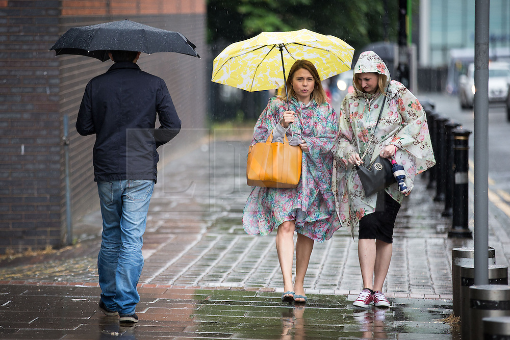 """© Licensed to London News Pictures . 02/07/2015 . Manchester , UK . Two women wearing ponchos arriving in the rain at the Castlefield Bowl at the opening of """" Summer in the City """" festival in Manchester. Photo credit : Joel Goodman/LNP"""