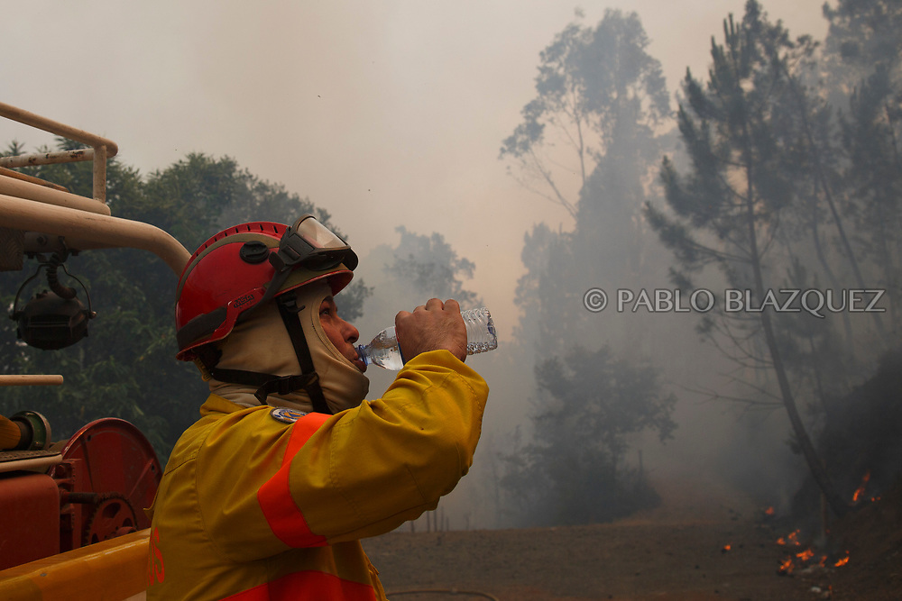 LEIRIA, PORTUGAL - JUNE 20:  A firefighter drinks water as he works to extinguish a fire in Mega Fundeira village after a wildfire took dozens of lives on June 20, 2017 near Picha, in Leiria district, Portugal. On Saturday night, a forest fire became uncontrollable in the Leiria district, killing at least 62 people and leaving many injured. Some of the victims died inside their cars as they tried to flee the area.  (Photo by Pablo Blazquez Dominguez/Getty Images)