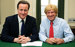 Leader of the Conservative Party David Cameron with Michael Fabricant, Member of Parliament for Lichfield in his office in Norman Shaw South, January 11, 2010. Photo By Andrew Parsons / i-Images.<br /> File Photo - Michael Fabricant blasted for tweet saying he would 'punch Yasmin Alibhai-Brown in the throat', photo filed Friday June 20th 2014.