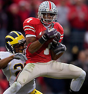 Ted Ginn pulls in a touchdown pass in front of Leon Hall of Michigan yesterday in the second quarter.