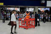 Blurred passengers pass a workman occupies a small fence during works on the concourse by the platforms in Waterloo station.