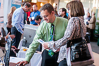 A business professional informs an event attendee about the services his company can supply