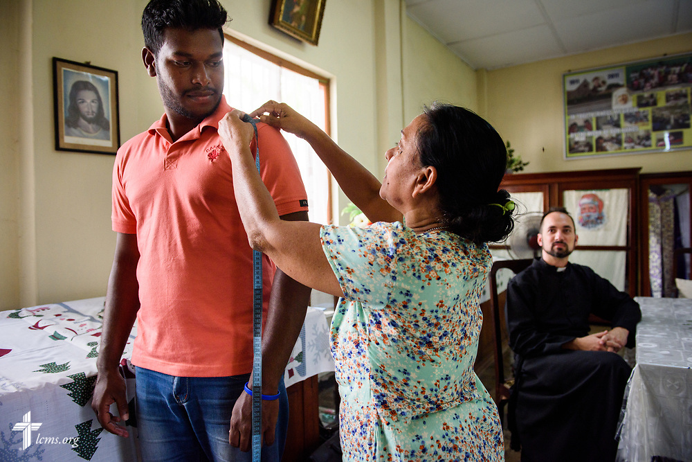 The Rev. Dr. Edward Naumann, LCMS career missionary and theological educator to South Asia, watches as Danshan, a pre-seminary student, is fitted for a cassock on Monday, Jan. 22, 2018, in Colombo, Sri Lanka. LCMS Communications/Erik M. Lunsford