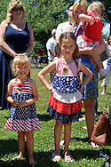 Wantagh, New York, USA. July 4, 2016. Young sisters are dressed in patriotic red white and blue dresses in the audience of the 60th Annual Miss Wantagh Pageant crowning ceremony, an Independence Day tradition on Long Island. Since 1956, the Miss Wantagh Pageant, which is not a beauty pageant, crowns an area high school student based mainly on academic excellence and community service.