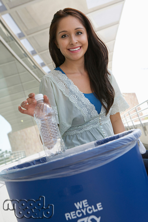 Young woman recycling plastic bottle, portrait