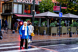 An old lady crosses the road in this street scene in the rain in Toulouse, France<br /> <br /> (c) Andrew Wilson | Edinburgh Elite media