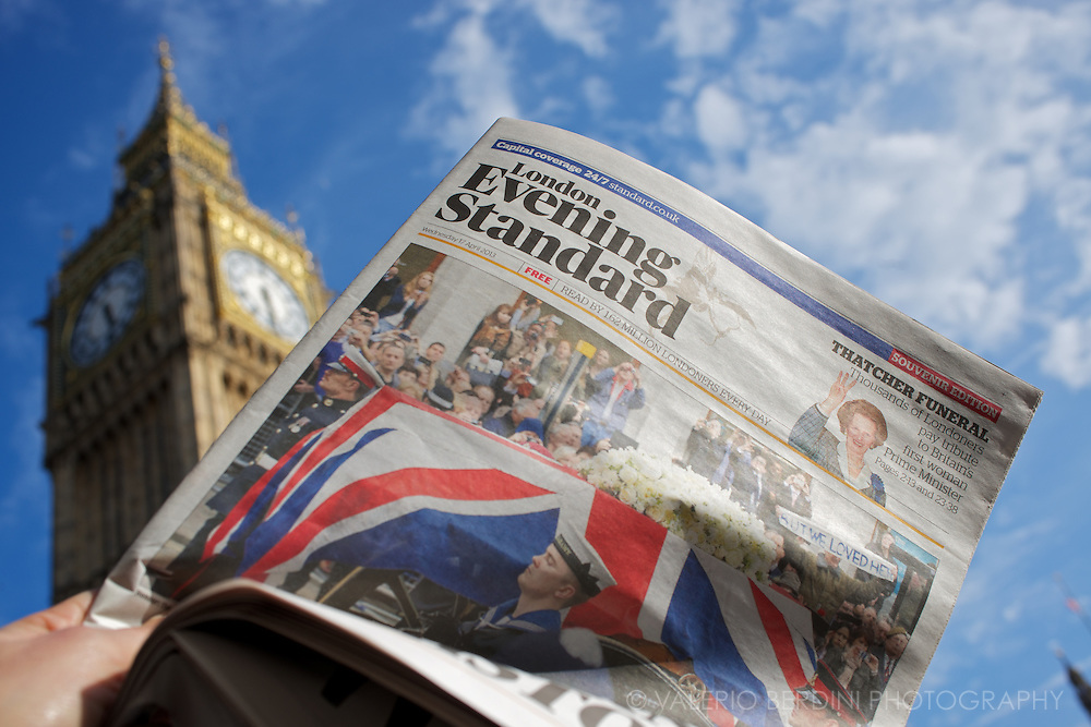 A commuter reads the Evening Standard in front of the Big Ben. Most of the paper copies are binned and become rubbish few hours after they have been printed.