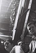 Youths under a fire escape, Manchester, UK, 1987.