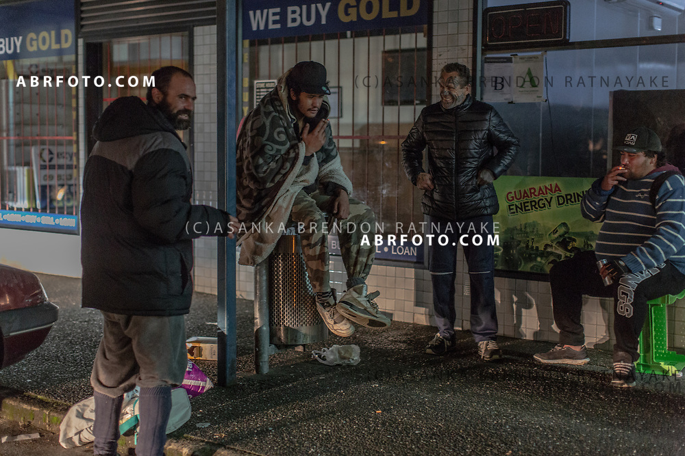 'Tu' sits on a bin at the Henderson shops and chats with other members of the homeless community in West Auckland on the 5th of June 2018. The Henderson shops is a popular meeting place for some of the homeless in West Auckland. Asanka Brendon Ratnayake for The New York Times.