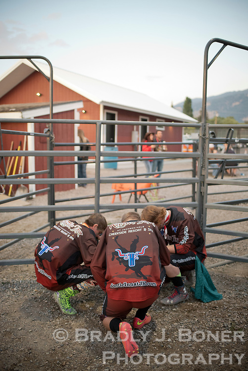 Rodeo clowns Seth Wilson, Steven Winer and Carson Miller share a quiet moment before the bull riding event at the Jackson Hole Rodeo.