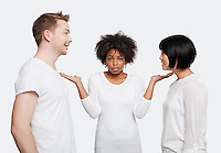 Portrait of young African American woman being ignored by friends over white background