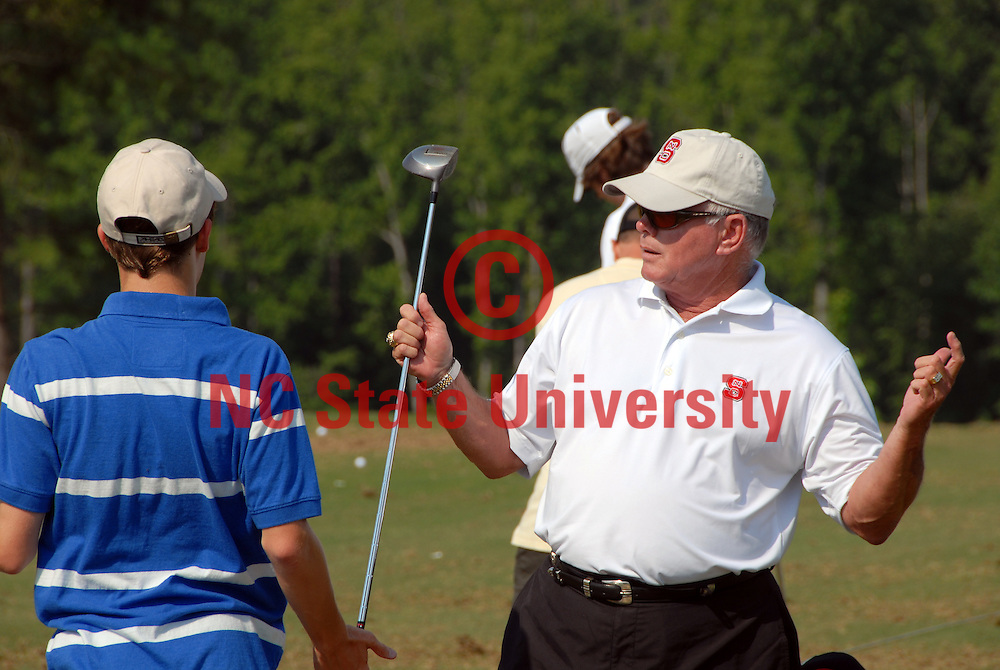 Mens head golf coach Richard Sykes (r) helps a camper at the Lonnie Poole Golf Course. PHOTO BY ROGER WINSTEAD