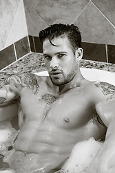 hot man with tattoos in a bathtub