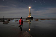 The Phare de Cordouan, or Cordouan Lighthouse, with light shining beneath a starry sky and a man watching the scene, built 1584-1611 in Renaissance style by Louis de Foix, 1530-1604, French architect, located 7km at sea, near the mouth of the Gironde estuary, Aquitaine, France. This is the oldest lighthouse in France. There are 4 storeys, with keeper apartments and an entrance hall, King's apartments, chapel, secondary lantern and the lantern at the top at 68m. Parabolic lamps and lenses were added in the 18th and 19th centuries. The lighthouse is listed as a historic monument. Picture by Manuel Cohen