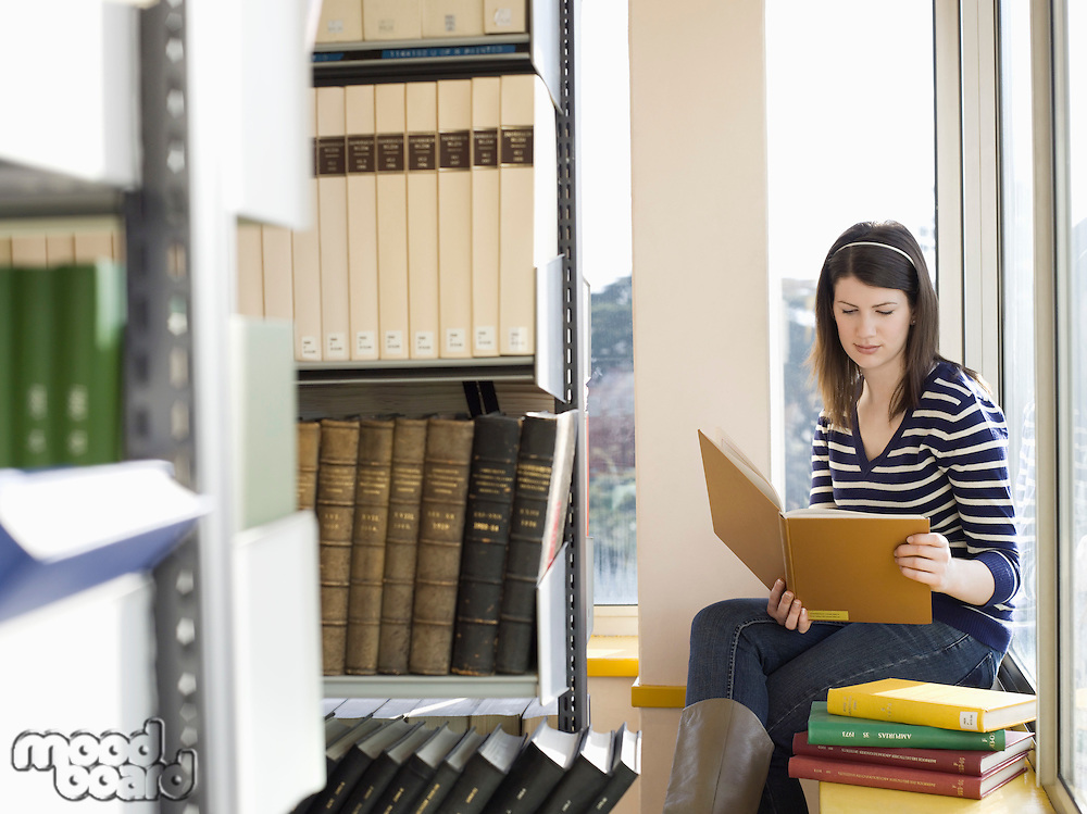 Student sitting on windowsill in library reading